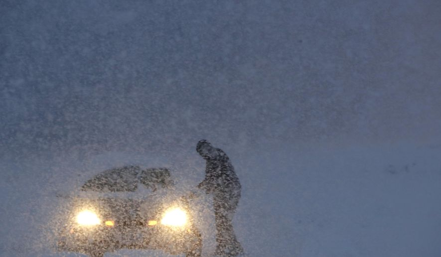 A man gets into a vehicle on a snowbank on the exit to a business along Route 23 during a snowstorm, Wednesday, March 7, 2018, in Wayne, N.J. (AP Photo/Julio Cortez)