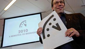 "FILE - In this Jan. 14, 2010 file photo, Lawrence Krauss, co-chair of the Bulletin of Atomic Scientists Board of Sponsors poses with a graphic image of the ""Doomsday Clock"" a during a news conference, in New York. Krauss, an Arizona State University physics professor, has been suspended from his job following allegations of groping, ogling and other sexual misconduct incidents. The school confirmed Wednesday, March 7, 2018, that Krauss is on paid leave and prohibited from campus while a review is conducted. (AP Photo/Mary Altaffer, File)"