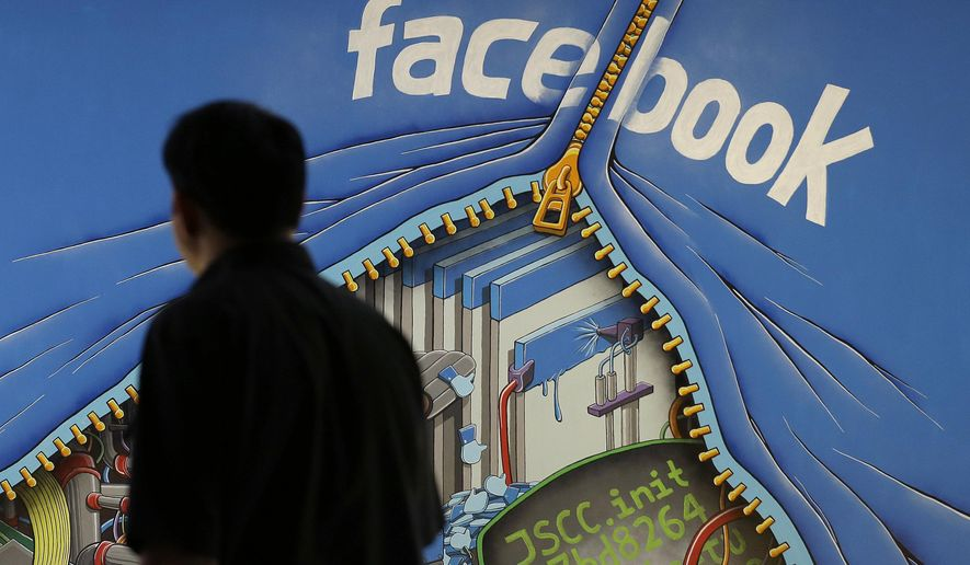 In this June 11, 2014, file photo, a man walks past a mural in an office on the Facebook campus in Menlo Park, Calif. (AP Photo/Jeff Chiu, File)