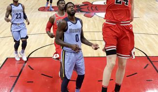 Chicago Bulls' Lauri Markkanen (24) dunks the ball as Memphis Grizzlies' JaMychal Green (0) watches during the first half of an NBA basketball game Wednesday, March 7, 2018, in Chicago. (AP Photo/Charles Rex Arbogast)