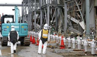 FILE - In this Nov. 12, 2014, file photo, workers wearing protective gears stand outside Fukushima Dai-ichi nuclear power plant's reactor in Okuma, Fukushima prefecture, northeastern Japan. A government-commissioned group of experts concluded Wednesday, March 7, 2018 that a costly underground ice wall is only partially effective in reducing the ever-growing amount of contaminated water at Japan's destroyed Fukushima nuclear plant, and that other measures are needed as well. (AP Photo/Shizuo Kambayashi, Pool, File)
