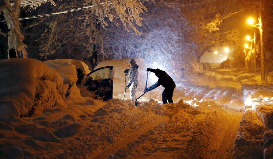 Residents on Mills Street dig out their car after a snowstorm dumped over a foot of snow around the area Wednesday, March 7, 2018, in Morristown, N.J. The storm carrying wind, rain and heavy snow was expected to continue into Wednesday night. (Bob Karp/The Record via AP)