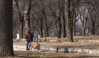 In this Monday, March 5, 2018, photo Ron Meyer and his dog, Seka, frequent users of Cooper Park, walk on the south side in Lincoln, Neb. (Gwyneth Roberts /Lincoln Journal Star via AP)