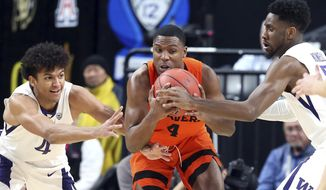 Washington's Matisse Thybulle, left, and Jaylen Nowell, right, and Oregon State's Alfred Hollins reach for a loose ball during the first half of an NCAA college basketball game in the first round of the Pac-12 men's tournament Wednesday, March 7, 2018, in Las Vegas. (AP Photo/Isaac Brekken)
