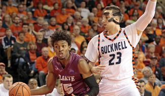 Colgate's Jordan Swopshire (15) drives on Bucknell's Zach Thomas (23) during the first half of an NCAA college basketball game for the Patriot League men's tournament championship in Lewisburg, Pa., Wednesday, March 7, 2018. (AP Photo/Chris Knight)