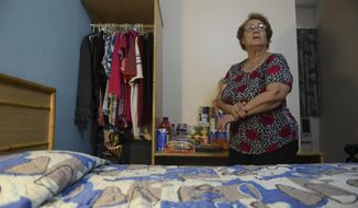 In this Monday, Feb. 26, 2018 photo, 69-year-old retiree Carmen Acosta stands in the hotel room she shares with her 44-year-old son, months after Hurricane Maria ripped the corrugated metal roof of her residence, in Cabo Rojo, Puerto Rico. So far, FEMA has provided $113 million in rental assistance to 129,000 people who were in Maria's path in Puerto Rico. (AP Photo/Carlos Giusti)