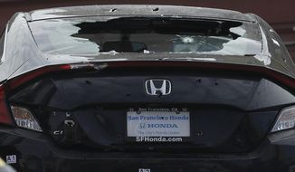 A shattered rear windshield appears on a vehicle as it is towed away in San Francisco, Wednesday, March 7, 2018. San Francisco police say officers who were investigating an armed robbery shot and killed a man who was hiding in the trunk of a car on Tuesday night. (AP Photo/Jeff Chiu)