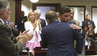 Rep. Jose Oliva, R- Miami Lakes, is hugged and congratulated by House members as the gun and school safety bill passed the Florida House 67-50 in Tallahassee, Fla., Wednesday, March 7, 2018. Oliva shepherd the bill through the House. (Scott Keeler/Tampa Bay Times via AP)