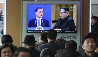 People watch a TV screen showing images of North Korean leader Kim Jong-un and South Korean President Moon Jae-in, left, at the Seoul Railway Station in Seoul, South Korea, Wednesday, March 7, 2018. (AP Photo/Ahn Young-joon)