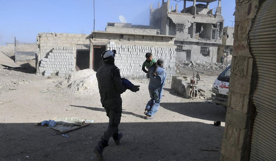 This photo released by the Syrian Civil Defense White Helmets, which has been authenticated based on its contents and other AP reporting, shows a member of the Syrian Civil Defense group carrying a victim after airstrikes and shelling hit in Ghouta, a suburb of Damascus, Syria, Wednesday, March. 7, 2018. Government forces carried out punishing airstrikes against an opposition-held suburb of Damascus, seeking to divide the besieged enclave in two and further squeeze rebels and tens of thousands of civilians trapped inside, state-run media and opposition activists reported. (Syrian Civil Defense White Helmets via AP) ** FILE **