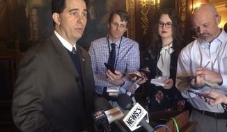 FILE - In this Feb. 14, 2018, file photo, Wisconsin Gov. Scott Walker, speaks to reporters in Madison, Wis. Senate Majority Leader Scott Fitzgerald said Wednesday, March 7, 2018, that changes will be needed to an $80 million juvenile justice overhaul plan that passed the Assembly unanimously and is a top priority of Gov. Scott Walker. Walker, who is up for re-election in November, has been negotiating with lawmakers on the juvenile justice bill. (AP Photo/Scott Bauer, File)