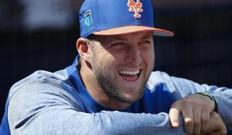 New York Mets' Tim Tebow laughs with teammates in the dugout before a spring training baseball game against the New York Yankees, Wednesday, March 7, 2018, in Port St. Lucie, Fla.. Tebow did not play. (AP Photo/John Bazemore)