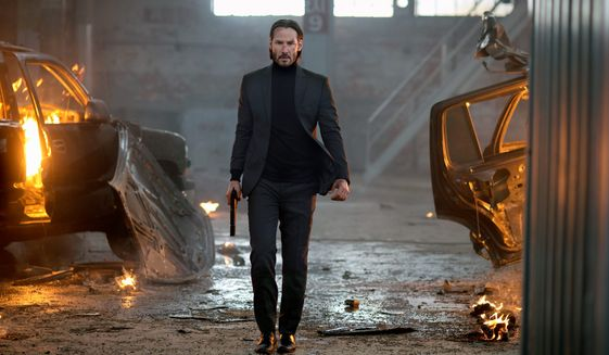 "Keanu Reeves carries a firearm in a dramatic scene of ""John Wick."" (Associated Press/File)"