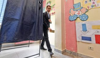 Five-Star movement's candidate premier Luigi Di Maio holds his ballot at a polling station in Pomigliano d'Arco, near Naples, Italy, Sunday, March 4, 2018.  More than 46 million Italians were voting Sunday in a general election that is being closely watched to determine if Italy would succumb to the populist, anti-establishment and far-right sentiment that has swept through much of Europe in recent years. (Ciro Fusco/ANSA via AP)