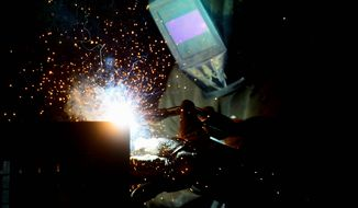 A welder fabricates a steel structure at an iron works facility in Ottawa, Ontario. (Sean Kilpatrick/The Canadian Press via AP)