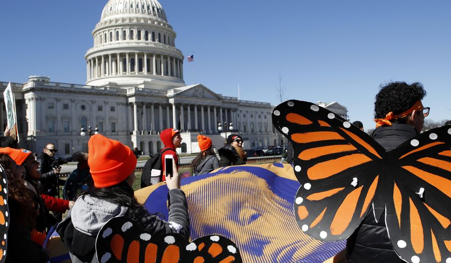 "Wearing ""butterfly wings,"" supporters of the Deferred Action for Childhood Arrivals (DACA) program hold a tarp with an image of President Donald Trump as they march in support of DACA, Monday, March 5, 2018, on Capitol Hill in Washington. (AP Photo/Jacquelyn Martin) ** FILE **"