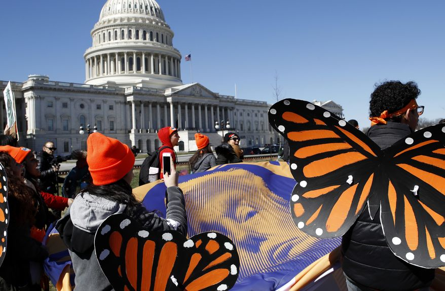 """Wearing """"butterfly wings,"""" supporters of the Deferred Action for Childhood Arrivals (DACA) program hold a tarp with an image of President Donald Trump as they march in support of DACA, Monday, March 5, 2018, on Capitol Hill in Washington. (AP Photo/Jacquelyn Martin) ** FILE **"""