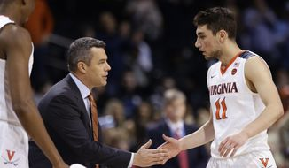 Virginia head coach Tony Bennett talks to Ty Jerome (11) during the first half of an NCAA college basketball game against Louisville in the quarterfinal round of the Atlantic Coast Conference tournament Thursday, March 8, 2018, in New York. (AP Photo/Frank Franklin II) ** FILE **