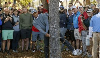 Tiger Woods hits from behind a tree on the fourth hole during the first round of the Valspar Championship golf tournament Thursday, March 8, 2018, in Palm Harbor, Fla. (AP Photo/Mike Carlson)