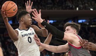 Xavier forward Tyrique Jones (0) looks to pass the ball around St. John's forward Amar Alibegovic (10) during the first half of an NCAA college basketball game in the quarterfinals of the Big East conference tournament, Thursday, March 8, 2018, at Madison Square Garden in New York. (AP Photo/Mary Altaffer)