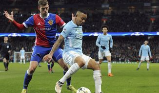 Manchester City's Gabriel Jesus, center, challenges for the ball with Basel's Fabian Frei during the Champions League, round of 16, second leg soccer match between Manchester City and Basel at the Etihad Stadium in Manchester, England, Wednesday, March 7, 2018. (AP Photo/Rui Vieira)