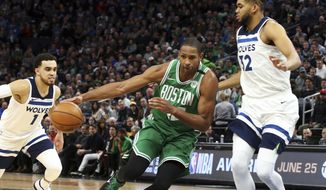 Boston Celtics's Al Horford, left, of Dominican Republic, tries to control the ball as he drives into Minnesota Timberwolves' Karl-Anthony Towns, right, in the first half of an NBA basketball game Thursday, March 8, 2018, in St. Paul, Minn. (AP Photo/Jim Mone)