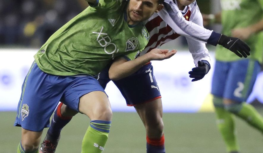 Seattle Sounders midfielder Cristian Roldan, left, is challenged by Guadalajara midfielder Orbelin Pineda during the first half of a CONCACAF Champions League soccer match Wednesday, March 7, 2018, in Seattle. (AP Photo/Ted S. Warren)