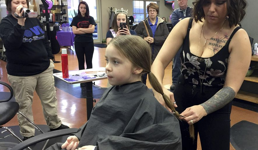 In this Feb. 5, 2018 photo, Montana Schmidt, right, a stylist at Kevin & Co. cuts the hair of  Sophia Wright at the salon in Danville. Ill., as part of Sophia's donation to Pantene's Beautiful Lengths program, which provides free wigs to cancer patients. Sophia inspired at least eight other children and adults to make a hair donation. (Noelle McGee/The News-Gazette via AP )