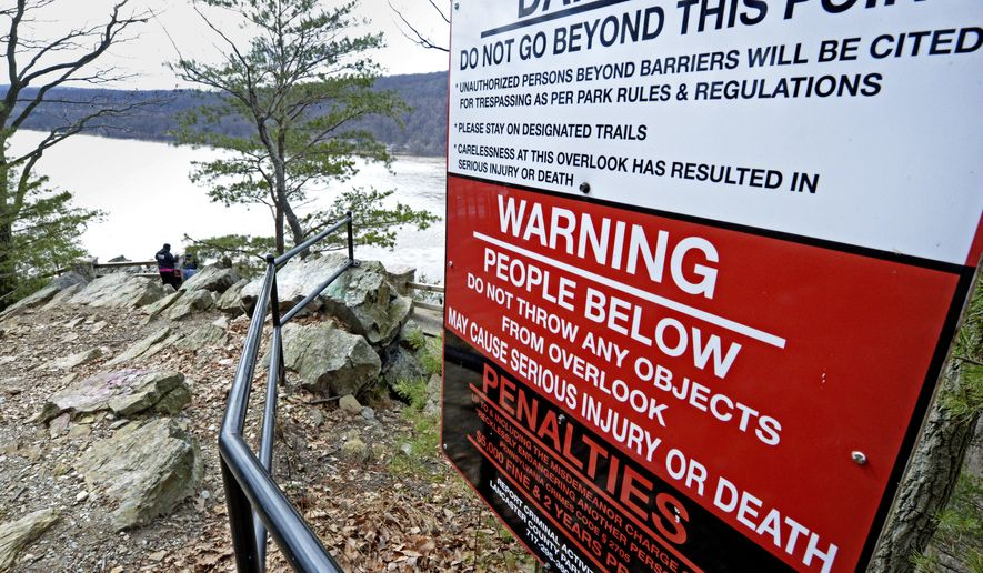 ADVANCE FOR USE SATURDAY, MARCH 10, AND THEREAFTER - In this Feb. 26, 2018 photo, a sign at the top of a Susquehanna River overlook warns visitors not to throw items from the vista because they might hit people using a section of the 14-mile Northwest Lancaster County River Trail below that opened in October 2016, in Chickies Rock County Park in Columbia, Pa. For private and public managers of natural areas working to keep natural landmarks open and accessible, yet safe for the public and uncluttered by signs and fences, the threat of liability is always in the background despite a Pennsylvania law aimed at protecting those who provide public recreation. (Blaine Shahan /LNP via AP)