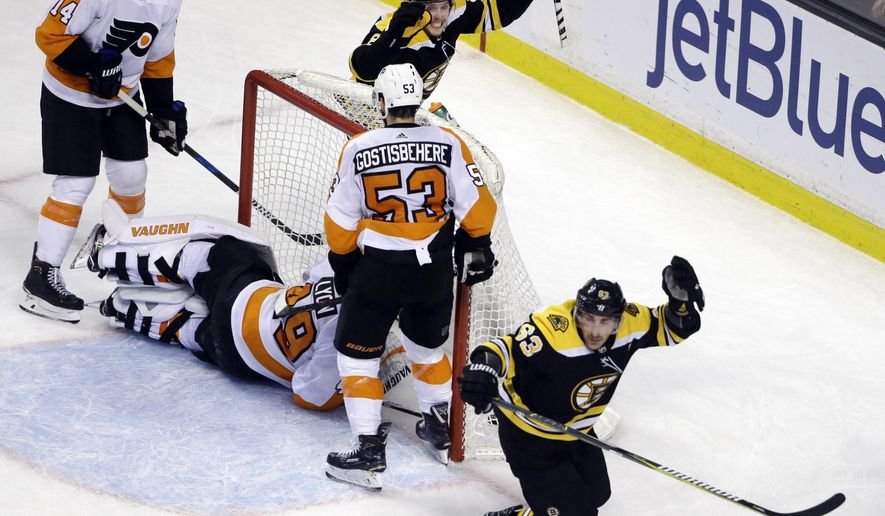 Boston Bruins left wing Brad Marchand, right, celebrates his goal along with Bruins right wing David Pastrnak as Philadelphia Flyers goaltender Alex Lyon (49), center Sean Couturier (14) and defenseman Shayne Gostisbehere (53) react in the final minute of an NHL hockey game Thursday, March 8, 2018, in Boston. The Bruins won 3-2. (AP Photo/Elise Amendola)