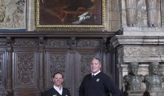 "In this undated photo provided by Hearst Castle/California State Parks are guides Laurel Rodger and Carson Cargill posing below the ""Annunciation"" painting hanging at Hearst Castle in San Simeon, Calif. The painting, that has been hanging at California's landmark Hearst Castle for decades, has been identified as a 17th century work thanks to two guides who noticed a previously undetected monogram and inscription when it was illuminated by late afternoon sunlight last fall. (Victoria Garagliano/Hearst Castle/California State Parks via AP)"