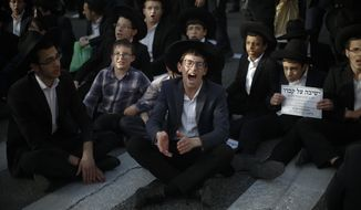 Ultra orthodox Jews block the entrance toJerusalem during a military draft protest, Thursday, March 8, 2018. Israel has compulsory military service for most Jewish men, but the ultra-Orthodox, whose political parties enjoy an outsized role in the country's coalition politics, have secured exemptions. Authorities still require ultra-Orthodox men to register for the draft, something to which the protesters gathered Thursday are opposed. (AP Photo/Ariel Schalit)