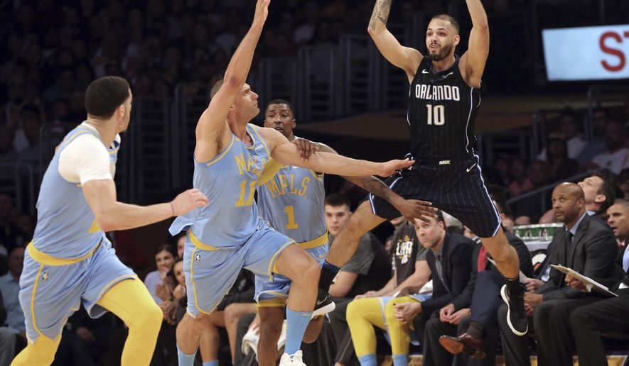 Orlando Magic's Evan Fournier (10) passes the ball over Los Angeles Lakers, including center Brook Lopez (11), during the first half of an NBA basketball game in Los Angeles on Wednesday, March 7, 2018. (AP Photo/Reed Saxon)