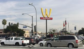 """Motorists make their way past a McDonald's restaurant with a flipped Golden Arches sign Thursday, March 8, 2018, in Lynwood, Calif. McDonald's has temporarily flipped its famous Golden Arches to look like a """"W,"""" a move it says it made to recognize International Women's Day. (AP Photo/Amanda Myers)"""