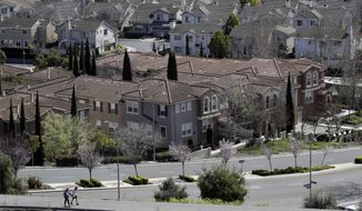 In this Tuesday, March 6, 2018, photo people walk along a path in front of a row of homes in San Jose, Calif. NerdWallet calculated affordability for 173 metropolitan areas by comparing the median annual household income and the monthly principal-and-interest payment for a median-priced single-family home and found that the least affordable homes are in the San Jose.(AP Photo/Marcio Jose Sanchez)