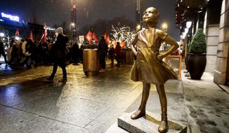 """A replica of the """"Fearless girl"""" sculpture by US artist Kristin Visbal stands in front of Grand Hotel in Oslo, Thursday 8 March, 2018. The sculpture was unveiled earlier Thursday. (Lise Aserud/NTB scanpix via AP)"""