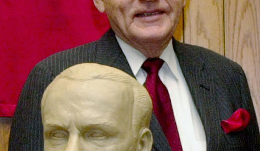 FILE - In this Feb. 22, 2003 file photo, former Neb. Governor, Charles Thone stands behind his clay bust in Lincoln, Neb., as the University of Nebraska-Lincoln College of Law paid tribute to five alumni governors. Thone, a former Nebraska governor and congressman who helped investigate the assassinations of President John F. Kennedy and Martin Luther King Jr., has died. He was 94. Thone's law partner and longtime friend, Mark Schorr, said Thone died Wednesday, March 7, 2018, of natural causes at his home in Lincoln. (AP Photo/Nati Harnik File)