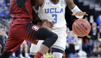 Stanford's Daejon Davis, left, covers a drive from UCLA's Aaron Holiday during the first half of an NCAA college basketball game in the quarterfinals of the Pac-12 tournament Thursday, March 8, 2018, in Las Vegas. (AP Photo/Isaac Brekken)