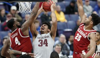 Texas A&M's Tyler Davis (34) heads to the basket as Alabama's Daniel Giddens (4) and Braxton Key (25) defend during the first half in an NCAA college basketball game at the Southeastern Conference tournament Thursday, March 8, 2018, in St. Louis. (AP Photo/Jeff Roberson)
