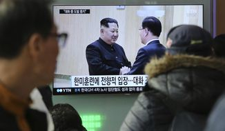 "People watch a TV screen showing North Korean leader Kim Jong Un, left, meeting with South Korean National Security Director Chung Eui-yong in Pyongyang, North Korea, at the Seoul Railway Station in Seoul, South Korea, Wednesday, March 7, 2018. After years of refusal, North Korean leader Kim Jong Un is willing to discuss the fate of his atomic arsenal with the United States and has expressed a readiness to suspend nuclear and missile tests during such talks, a senior South Korean official said Tuesday. Korean characters seen on the screen read: ""South Korea-U.S. joint military drills."" (AP Photo/Ahn Young-joon)"