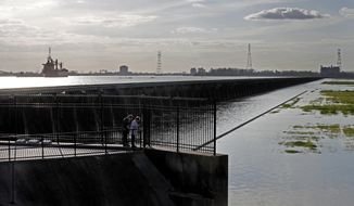 FILE - In this March 5, 2018, file photo, people look at the inside of the Bonnet Carre Spillway, as ships along the rising Mississippi River are seen on the other side of the floodgates, in Norco, La. The U.S. Army Corps of Engineers will open part of the Bonnet Carre Spillway on Thursday, March 8, 2018. (AP Photo/Gerald Herbert, File)