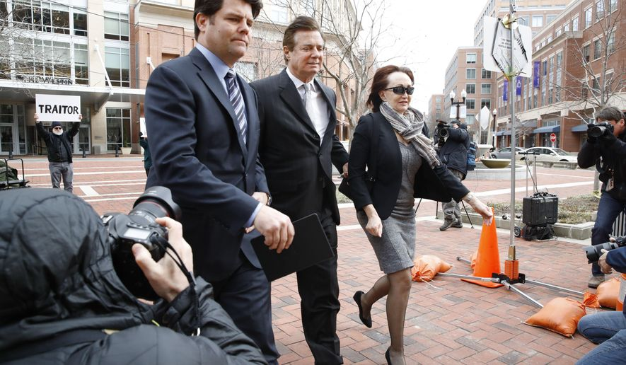 Paul Manafort, center, President Donald Trump's former campaign chairman, walks with this wife Kathleen Manafort, as they arrive at the Alexandria Federal Courthouse for an arraignment hearing on his Eastern District of Virginia charges, in Alexandria, Va., Thursday, March 8, 2018.  Jason Maloni, Manafort's spokesman, is at left.  (AP Photo/Jacquelyn Martin)