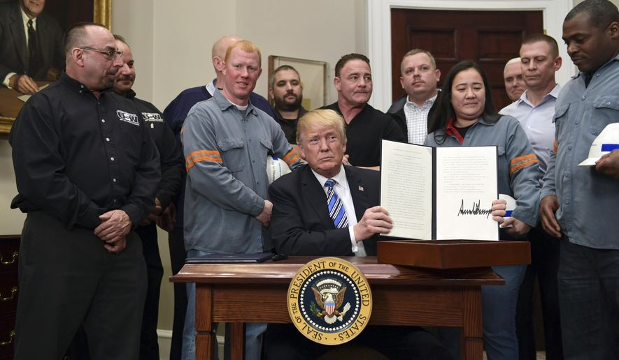 President Donald Trump holds up a proclamation on steel imports during an event in the Roosevelt at the White House in Washington, Thursday, March 8, 2018. He also signed one for aluminum imports. (AP Photo/Susan Walsh)