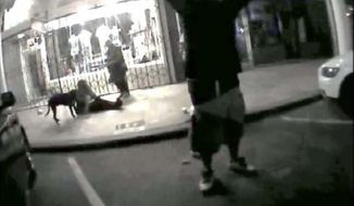 In this May 5, 2017 image  from a police body worn video camera released by the Los Angeles County District Attorney's Office, Brendon Glenn is shown with his arms in the air yelling before being shot by police near the Venice boardwalk in Los Angeles. A police officer who shot and killed an unarmed homeless man near the Venice boardwalk last year violated departmental policy, the Police Commission ruled Tuesday, March 6, 2018. The civilian panel concluded that Officer Clifford Proctor wasn't justified in shooting Brendon Glenn twice in the back as Glenn, 29, was on the ground last May 5. The officers tried to detain Glenn after reports that he had been harassing people and they saw him struggling with a bar bouncer, police said. (Los Angeles District Attorney's Office via AP)