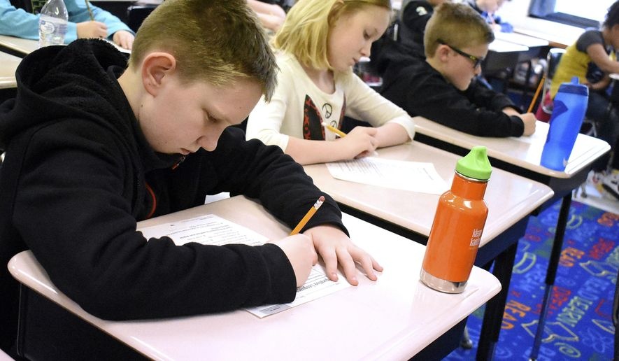 Pleasant Valley fourth graders Connor Atkins, left, Makenna Laymon-Cutlip, and Cooper Kuneff work on their Language assignment on the first day back to class following the teachers strike Wednesday, March 7, 2018, in Pleasant Valley, W.Va. Students returned Wednesday to schools across West Virginia, a day after the state's teachers wangled a 5 percent pay increase from their elected leaders. Their victory came after walking off the job in all 55 counties of this poor Appalachian mountain state to protest some of the lowest pay for their profession in the country. (Tammy Shriver/Times-West Virginian via AP)
