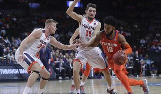 Clemson guard Gabe DeVoe (10) drives against Virginia center Jack Salt (33) and guard Ty Jerome (11) during the first half of an NCAA college basketball game in the Atlantic Coast Conference men's tournament semifinals Friday, March 9, 2018, in New York. (AP Photo/Julie Jacobson)