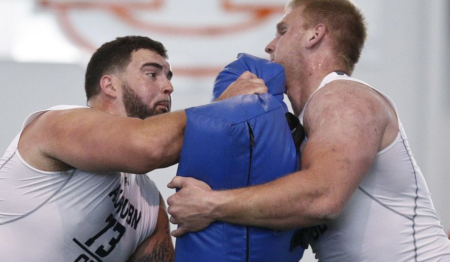 Auburn's offensive lineman Austin Golson, left and Braden Smith run drills during Auburns Pro Day, Friday, March 9, 2018, in Auburn, Ala. The event is to showcase players for the upcoming NFL football draft. (AP Photo/Brynn Anderson)