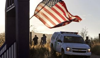 In this Dec. 15, 2010, file photo an American flag flutters in the wind on a nearby resident's home near a U.S. Border Patrol vehicle near where agent Brian Terry was killed, northwest of Nogales, Ariz. (Greg Bryan /Arizona Daily Star via AP, File)