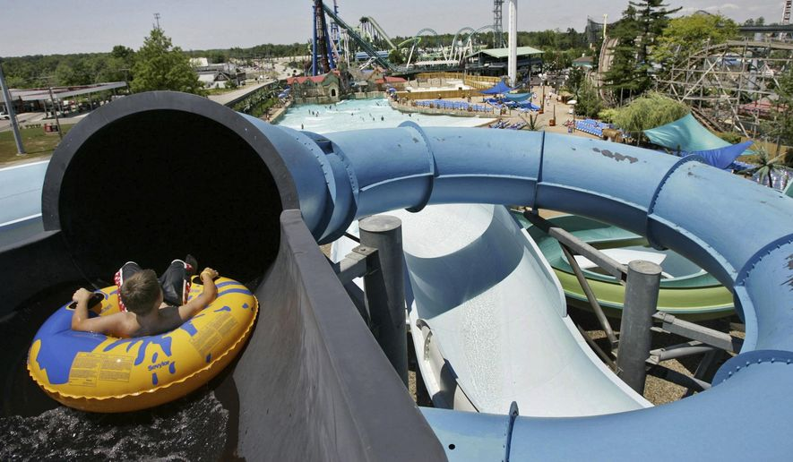 FILE - In this June 22, 2005, file photo, Josh Bingham begins riding down a waterslide, with roller coasters visible in the distance, in the Hurricane Hannah section of Geauga Lake Park in Aurora, Ohio. Geauga Lake Park closed abruptly after the 2007 season, but Brian Roote, of Independence, Ohio, started an online fundraising campaign in February 2018, hoping to raise $20 million to buy what's left of the amusement park and save it from extinction. (AP Photo/Amy Sancetta, File)