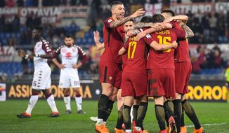 AS Roma's Daniele De Rossi, second from right with back to camera, is hugged by teammates as he celebrates after scoring during a Serie A soccer match between AS and Torino, at the Olympic stadium, in Rome, Friday, March 9, 2018.  (Alessandro Di Meo/ANSA via AP)